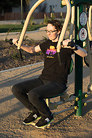 A woman wearing black uses the Greenfields outdoor bodyweight exercise equipment at State Street Park.  Model release potentially available.