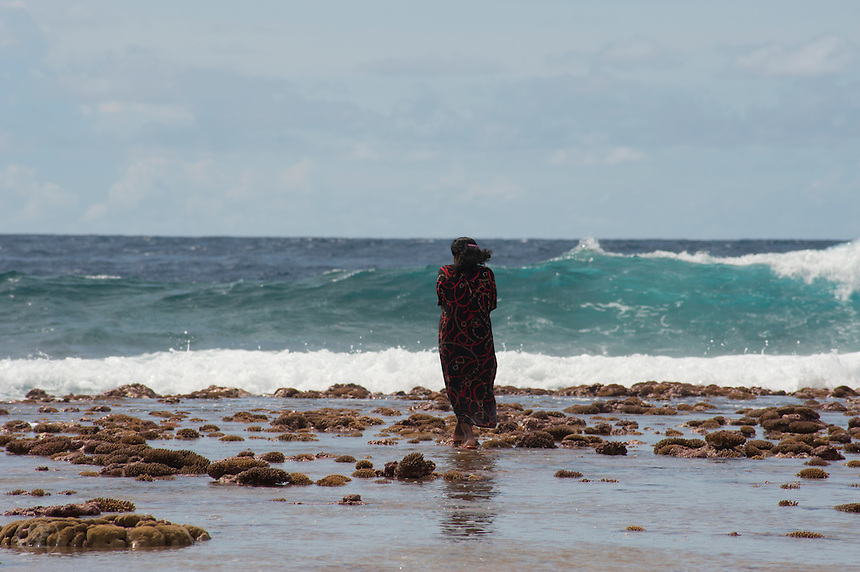 A Marshallese woman picks her way along the edge of the ocean side reef on Jaluit Atoll, collecting shellfish as the tide changes and begins to wash shells ashore. With a mean sea level of just 2 metres, the Marshall Islands are at severe risk from sea level rise.