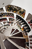 A glimpse into the concealed wine cellar reveals orderly shelves of bottles lining a spiral staircase