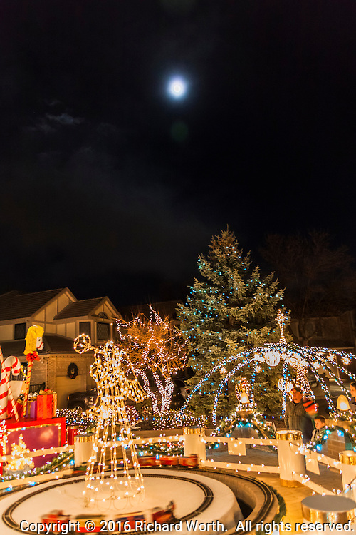 The day before the Full Cold Moon, the nearly full moon shines over the opulent holiday lights displayed at the end of a neighborhood cul-de-sac.