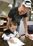 Stormtrooper Lincoln Fowler, 3, colors with his dad Joshua during the Star Wars Day celebration at the Carson City Library in Carson City, Nev. on Wednesday, May 4, 2016.<br />