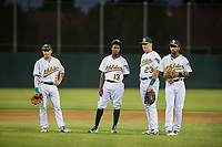 AZL Athletics infielders Nick Allen (2), Marcos Brito (13), Chris Iriart (23), and Yerdel Vargas (5) talk while relief pitcher Jose Mora (not pictured) warms up during a game against the AZL Brewers on August 18, 2017 at Lew Wolff Training Complex in Mesa, Arizona. AZL Brewers defeated the AZL Athletics 6-4. (Zachary Lucy/Four Seam Images)