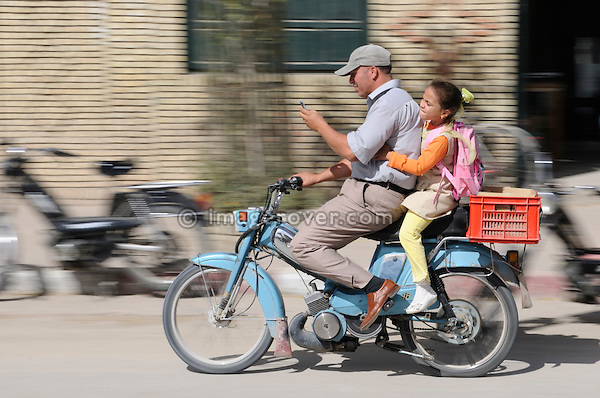 Africa, Tunisia, Tozeur. Tunisian father and doughter on moped while using mobile phone. --- No releases available, but releases may not be needed for certain uses. Automotive trademarks are the property of the trademark holder, authorization may be needed for some uses.