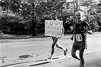 USA. New York. Central Park. Two men hold a Happy Birthday sign while jogging. © 1985 Didier Ruef