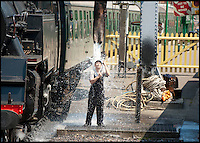 BNPS.co.uk (01202) 558833<br /> Picture: Peter Willows/BNPS<br /> <br /> Volunteer train driver Peter Frost (55) takes drastic action to keep cool by having a shower from the water tower at the Swanage Railway station in Dorset. Temperatures onboard the No. 80104 British Railways Class 4 steam loco have been stifling, and Peter, who grew up in Corfe Castle and used to ride on the footplates on the line from Wareham to Swanage in the 1960s, took the shower to cool off before resuming his journey.