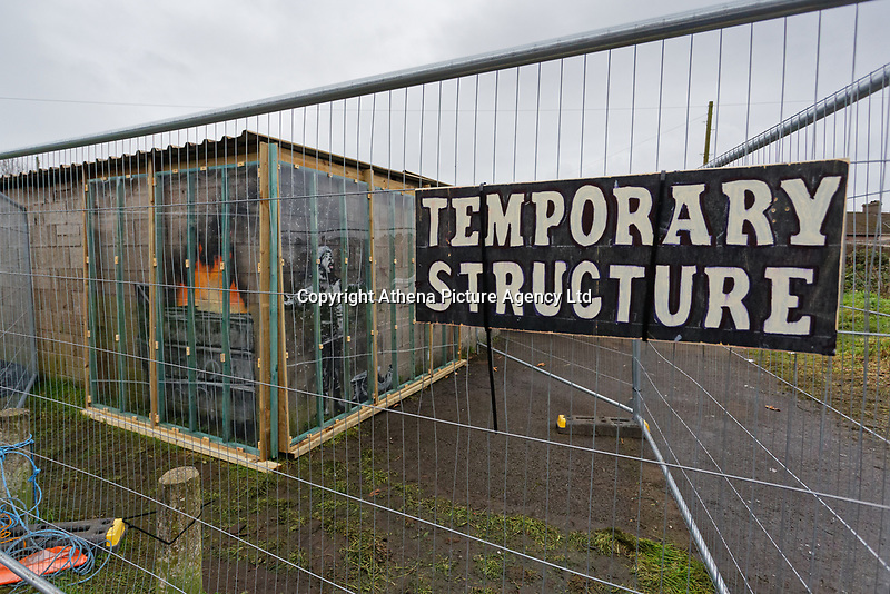 """Pictured: A """"Temporary Structure"""" sign on the fence protecting the Banksy graffiti on a garage in Port Talbot, Wales, UK. Tuesday 25 December 2018<br /> Re: The artist Banksy has confirmed that a new graffiti piece that has appeared in Port Talbot, south Wales is his.<br /> He announced on Instagram: """"Season's greetings"""" - with a video of the artwork in the Taibach area of Port Talbot.<br /> The image appears on two sides of a garage in a lane near Caradog Street, depicting a child enjoying snow falling - the other side reveals it is a fire emitting ash.<br /> The owner of the garage said he had not slept over fears it might be vandalised."""
