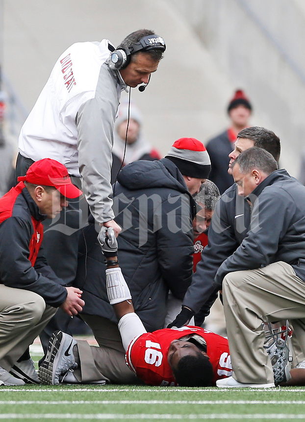 Ohio State Buckeyes head coach Urban Meyer grabs the hand of quarterback J.T. Barrett (16) after he went down with an ankle injury during the 4th quarter of the NCAA football game at Ohio Stadium on Nov. 29, 2014. (Adam Cairns / The Columbus Dispatch)
