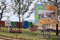 "Rwanda. Kigali province. Kigali. Downtown. Town center. Men and women walk close to the construction site of a eight floors commercial building.  A giant advertisement board advices the people to invest in buying now a private house. Sale of property.  "" Must house. Buy it nows. Legacy for your family."" Real estate. © 2007 Didier Ruef"