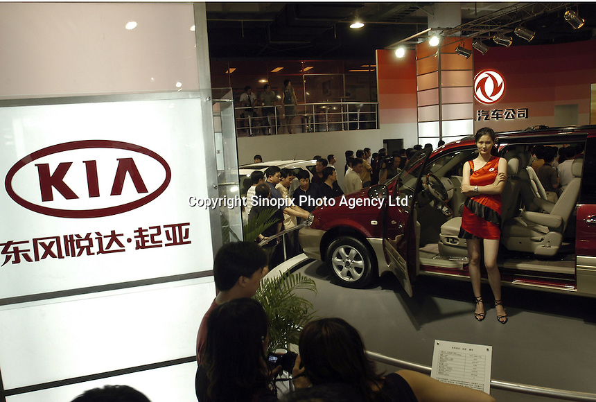 A model poses besides a car from Dongfeng Yueda Kia at the Auto China 2004 exhibition in Beijing, China..