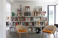 A pair of 1950s armchairs is placed in front of a 'Stacked' modular bookcase in the open plan living room