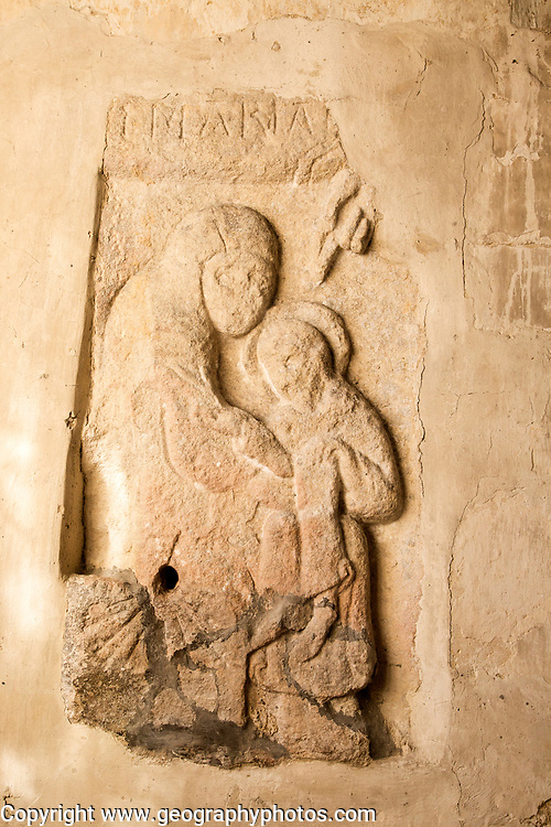 Early Anglo - Saxon stone carved figure of Virgin Mary and child Jesus Christ, building interior medieval church architectural feature, Inglesham, Wiltshire, England,