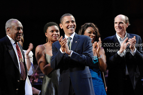 Washington, DC - March 8, 2009 -- United States President Barack Obama (C) joins performers (including host Bill Cosby (L) and James Taylor (R)) on stage to lead in singing 'Happy Birthday' to Senator Ted Kennedy (Democrat- Massachusetts)  at a musical tribute to celebrate Kennedy's birthday at the Kennedy Center in Washington, DC., USA, on Sunday, 08 March 2009.  .Credit: Chris Usher - Pool via CNP