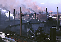 Smoke and dust pour out of Gary Steel Works, US Steel Corporation, Gary Indiana, 1966. Gary Steel Works covered approximately 1500 acres of the south shore of Lake Michigan (visibile back right), employed nearly 20,000 workers and operated around the clock, 365 days a year. Photo by John G. Zimmerman.