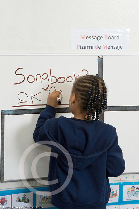 Education Preschool 4-5 year olds girl at dry erase board writing name under job for day, picking song for circle time