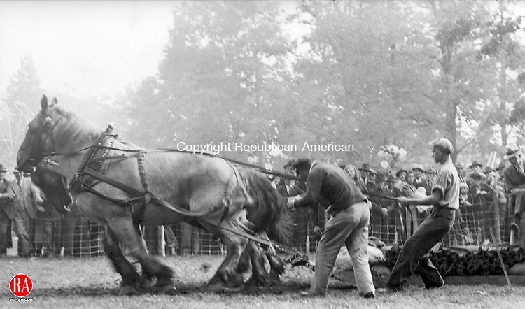 DURHAM - In this undated photo of the Durham Fair, a pair of horses works hard to pull a heavy load while spectators gather to watch.