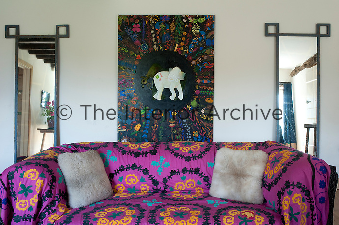 The decoration of the house is a mixture of reclamation and junk shop finds with the living room sofa covered in bright Afghan throws