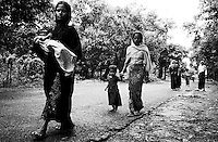 A group of Rohingya women walk with their children into the town of Teknaf where they will beg for food. After Bangladesh authorities arrested their husbands, most of the women in the group have not seen their husbands in months.