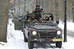 Foto: VidiPhoto<br /> <br /> SCHAARSBERGEN – Terwijl collega's bij de warme kachel een 'NAVO-vertegenwoordiger' beschermen, staan en zitten de overige militairen dik ingepakt te kleumen in hun open voertuigen in de sneeuw. De bossen bij Schaarsbergen (gemeente Arnhem) vormden donderdag het decor voor de eindoefening van het Force Protection Peloton van het Bataljon Limburse Jagers uit Oirschot dat in maart vertrekt naar Afghanistan. De pantserinfanteristen werken in Afghanistan samen met Duitse militairen met als doel de achtergebleven (NAVO-)veiligheidsadviseurs uit 30 verschillende landen te beschermen bij hun werkzaamheden in Afghanistan. Die ondersteunen niet alleen Afghaanse veiligheidstroepen, maar ook verrichten ook advieswerk op het gebied van de infrastructuur om zo het land weer op te bouwen.