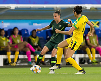 GRENOBLE, FRANCE - JUNE 18: Chloe Logarzo #6 of the Australian National Team dribbles as Chantelle Swaby #4 of the Jamaican National Team defends during a game between Jamaica and Australia at Stade des Alpes on June 18, 2019 in Grenoble, France.