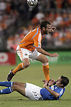 10 November 2007:  Brad Davis (top) of the Houston Dynamo jumps over the slide tackle of Davy Arnaud (22) of the Wizards.  The MLS Houston Dynamo defeated the Kansas City Wizards 2-0 at Robertson Stadium, Houston, Texas to capture the 2007 MLS Western Conference title and to advance to the MLS Cup championship final on Saturday, November 18th.