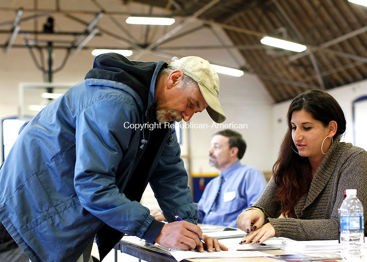"Torrington, CT- 27 March 2013-032713CM05-  Floyd Barto, left, of Torrington and a Army Veteran, files a claim for disability compensation at the Torrington Armory Wednesday afternoon.  Helping him is Simone Conforto, Homeless Coordinator with the Hartford Regional Office for the Veterans Benefit Administration.  Around 300 veterans visited the armory on Wednesday during ""Stand Down 2013"", which was sponsored by the Torrington chapter of FISH (Friends in Service to Humanity). The event provided free services and helpful information from state and federal agencies, as well as local businesses and organizations.  Three barber chairs were set up to give free hair cuts and lunch was also served said Deirdre DiCara, executive Director at FISH.  Stand Down is where homeless veterans and those in need, receive help and the services they need all in one place.     Christopher Massa Republican-American"