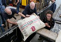 Nederland Amsterdam 2017. In een klein fabriekje in Amsterdam-Noord maken de Chocolatemakers zo eerlijk en duurzaam mogelijke chocoladerepen. De ondernemers regelen zelf de inkoop en laten een zeilschip een flink deel van de cacao vervoeren, want dat is duurzamer dan een vrachtschip. Het schip de Tres Hombres wordt gelost met behulp van vrijwilligers. Naast cacaobonen worden er ook zakken met fairtrade koffie de kade op getild. Foto Berlinda van Dam / Hollandse Hoogte.