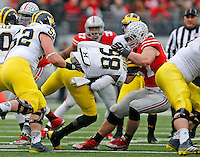 Ohio State Buckeyes defensive lineman Joey Bosa (97) brings down Michigan Wolverines quarterback Devin Gardner (98) during the fourth quarter of the NCAA football game against Michigan at Ohio Stadium on Saturday, November 29, 2014. (Columbus Dispatch photo by Jonathan Quilter)