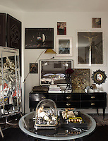 A glass cloche filled with miniature skulls prefaces a wall of artwork in the master bedroom