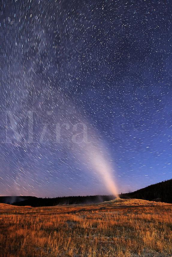 Old Faithful geyser erupting under starry sky, Yellowstone National Park, Wyoming, USA