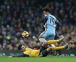 Leroy Sane of Manchester City skips over a sliding tackle by Granit Xhaka of Arsenal during the English Premier League match at the Etihad Stadium, Manchester. Picture date: December 18th, 2016. Picture credit should read: Simon Bellis/Sportimage