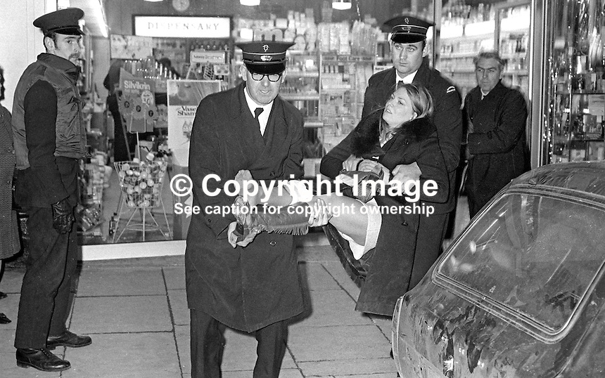 Ambulancemen carry an injured woman from McKay's pharmacy at Cliftonville Circus, Belfast, following a Provisional IRA gun attack on an RUC patrol car, 28th November 1971. Vivienne Gibney, 17 years, clerical worker, Deerpark Road, Belfast, died 4 days later 1st December 1971. She was standing outside a pharmacy when the gunmen opened fire. Vivienne Gibney is not the woman in this photograph. 197111280482..Copyright Image from Victor Patterson, 54 Dorchester Park, Belfast, United Kingdom, UK...For my Terms and Conditions of Use go to http://www.victorpatterson.com/Victor_Patterson/Terms_%26_Conditions.html