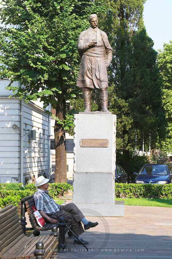 A statue of UNK and an old man with a walking stick sitting on a bench Podgorica capital. Montenegro, Balkan, Europe.