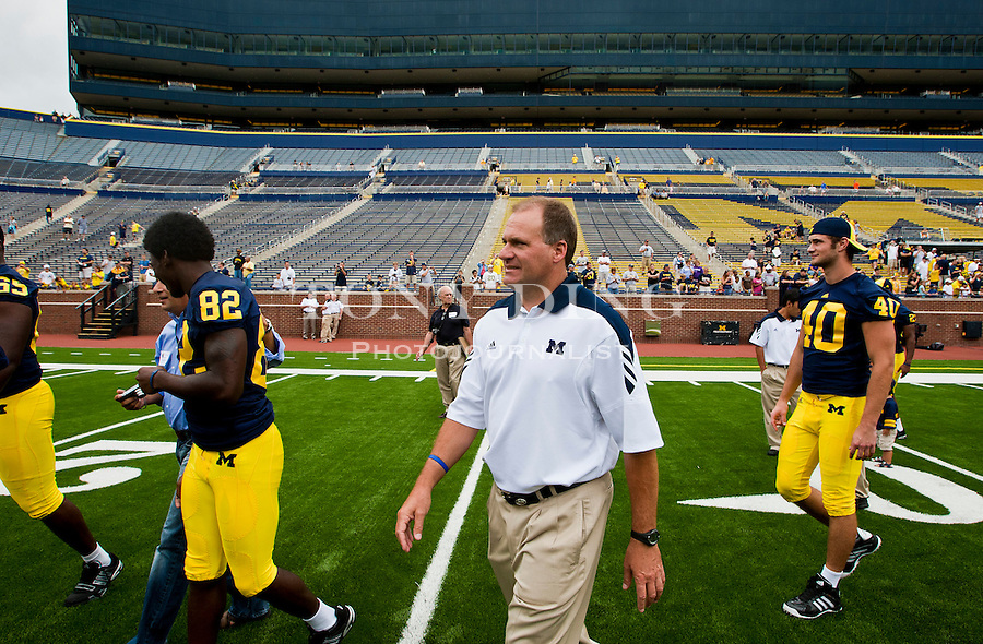Michigan head coach Rich Rodriguez walks the Michigan Stadium field with players to a team photo session, during the annual NCAA college football media day, Sunday, Aug. 22, 2010, in Ann Arbor, Mich. (AP Photo/Tony Ding)