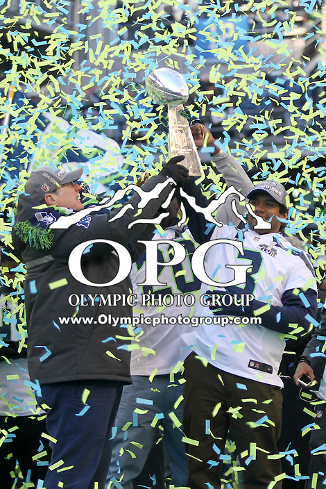 2014-02-05:  Seattle Seahawks owner Paul Allen and quarterback Russell Wilson hoist the Super Bowl trophy into the air.  Seattle Seahawks players and 12th man fans celebrated bringing the Lombardi trophy home to Seattle during the Super Bowl Parade at Century Link Field in Seattle, WA.