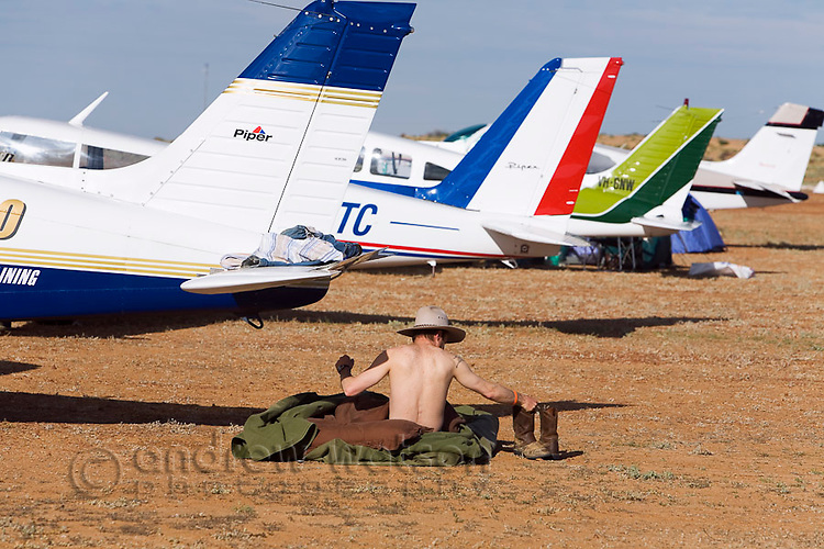 A man camps amidst the aircraft during the annual Birdsville Races.  Every September hundreds of aircraft arrive at the remote town for the most famous horse racing carnival in outback Australia.  Birdsville, Queensland, AUSTRALIA.