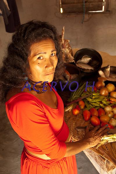 Carm&eacute;zia, &iacute;ndia Macuxi, prepara a damorida, comida ind&iacute;gena a base de peixes ou ca&ccedil;a temperada com forte molho apimentado.<br /> Comunidade ind&iacute;gena  Macux&iacute;, Raposa Serra do Sol.<br /> Normandia, Roraima, Brasil.<br /> Foto Paulo Santos<br /> <br /> 2004 Carm&eacute;zia Emiliano &eacute; ind&iacute;gena Macuxi e nasceu em 20 de abril na Guyana. Sua fam&iacute;lia imigrou para a aldeia Jap&oacute;, no munic&iacute;pio de Normandia, estado de Roraima, Brasil, na d&eacute;cada de 70 e desde 1988, ela reside em Boa Vista.<br /> <br /> A artista conquistou por quatro vezes o pr&ecirc;mio na Bienal de Arte Naif do Sal&atilde;o SESC de Piracicaba-SP e foi agraciada com o Pr&ecirc;mio Buriti da Amaz&ocirc;nia de Preserva&ccedil;&atilde;o do Meio Ambiente, em 1996, na categoria revela&ccedil;&atilde;o.<br /> <br /> Ela figura no topo da lista dos maiores artistas Naifs brasileiros. O estilo &eacute; conhecido por lan&ccedil;ar obras com aquele aspecto inacabado, primitivo, at&eacute; mesmo singelo e descompromissado.  A rela&ccedil;&atilde;o de Carm&eacute;zia com a arte est&aacute; intimamente relacionada com a sua trajet&oacute;ria. Ao conhecer as obras de arte e a vida da artista, t&ecirc;m-se a boa impress&atilde;o de que Carm&eacute;zia pinta a si pr&oacute;pria, em vida e em mem&oacute;ria.<br /> <br /> A mulher que nasceu e se criou na comunidade ind&iacute;gena, constituiu fam&iacute;lia com um pernambucano - L&eacute;o Malabarista - entrou com ele no mundo do circo e se integrou na cena urbana sem jamais esquecer o caminho de volta para sua ancestralidade
