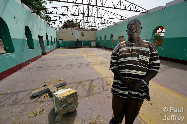 Father Karlo Kaw stands in the ruined sanctuary of the Our Lady of the Annunciation parish in Abyei, a town at the center of the contested Abyei region along the border between Sudan and South Sudan. The church building, along with adjoining residences, educational facilities and a warehouse for relief supplies, were damaged and looted in 2011 when soldiers and militias from the northern Republic of Sudan swept through the area, chasing out tens of thousands of residents. Although Ethiopian peacekeepers patrol the region, renewed attacks by northern-backed Misseriya militias in 2013 have Kaw and others worried. The African Union has proposed a new peace plan, including a referendum to be held in October 2013, but it has been rejected by the Misseriya and Khartoum. The Catholic parish of Abyei, with support from Caritas South Sudan and other international church partners, has maintained its pastoral presence among the displaced and assisted them with food, shelter, and other relief supplies. Yet Kaw and another priest have not officially returned to Abyei, remaining with most Abyei residents in Agok, some 25 kilometers to the south. Every Sunday one of them comes to celebrate Mass in Abyei, with church members gathering under a tree outside the desecrated sanctuary.