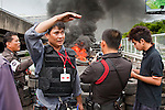 16 MAY 2010 - BANGKOK, THAILAND: Anti government protesters and Royal Thai Police  watch a tire barricade burn on Rama IV Road Sunday. Thai troops and anti government protesters clashed on Rama IV Road again Sunday afternoon in a series of running battles. Troops fired into the air and unidentified snipers shot at pedestrians on the sidewalks. At one point Sunday the government said it was going to impose a curfew only to rescind the announcement hours later. The situation in Bangkok continues to deteriorate as protests spread beyond the area of the Red Shirts stage at Ratchaprasong Intersection. Many protests now involve people who have not been active in the Red Shirt protests and live in the vicinity of Khlong Toei slum and Rama IV Road. Red Shirt leaders have called for a cease fire, but the government indicated that it is going to go ahead with operations to isolate the Red Shirt camp and clear the streets.      PHOTO BY JACK KURTZ