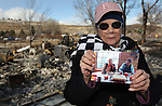 Standing in front of the rubble of her home on Saturday, Jan. 21, 2012, Jeannie Watts holds a picture of herself and her mother June Hargis who died Thursday as a wind-driven brush fire burned through Pleasant Valley, south of Reno, Nev.  The Watts also lost three horses in the fire. (AP Photo/Cathleen Allison)
