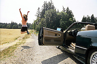 Young woman motorist leaping for joy..MR