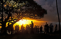 Sunset reception at Kapalua Bay, Maui with crowds of people silhouetted against the golden sky.