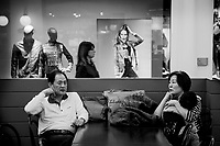Switzerland. Ticino. Mendrisio. A Chinese tourist family sits and rests inside the Foxtown. The mother holds her child asleep in her arms. FoxTown is a huge outlet commercial center where customers come to shop. 6.11.2016  © 2016 Didier Ruef