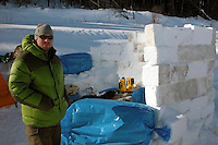 Keith Larson, an Iditarod volunteer, cut snow blocks to make a wind-break at Eagle Island. Photo by Jon Little.