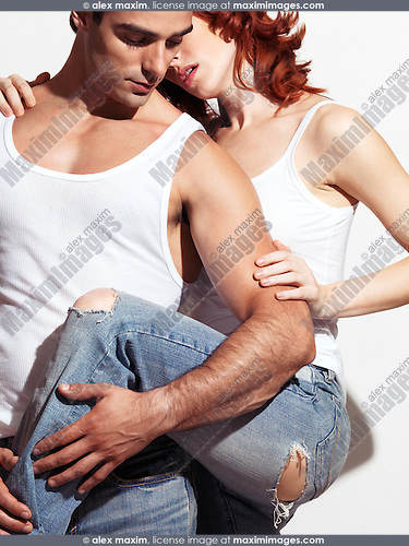 Sexy young couple in blue jeans and white tank tops on white background