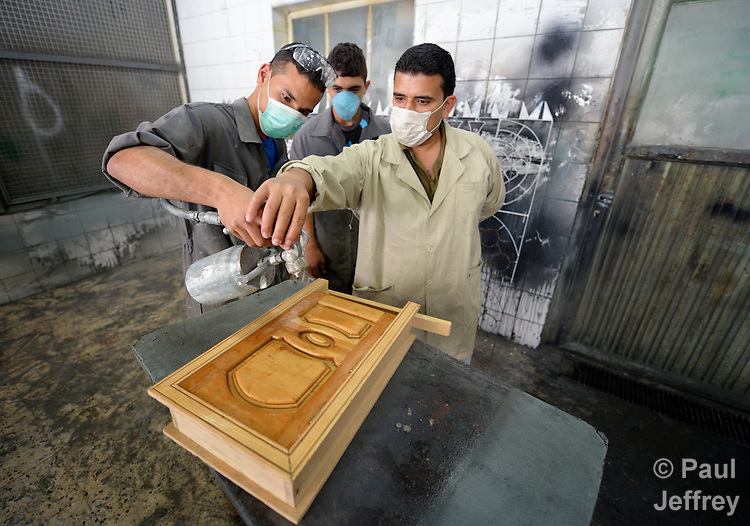 Instructor Ishamis Abu Mhasin helps students learn to spray warnish in a woodworking class in the Vocational Training Center in Gaza City, Gaza. The center is run by the Department of Service for Palestinian Refugees of the Near East Council of Churches, a member of the ACT Alliance, and funded in part by the Pontifical Mission for Palestine.