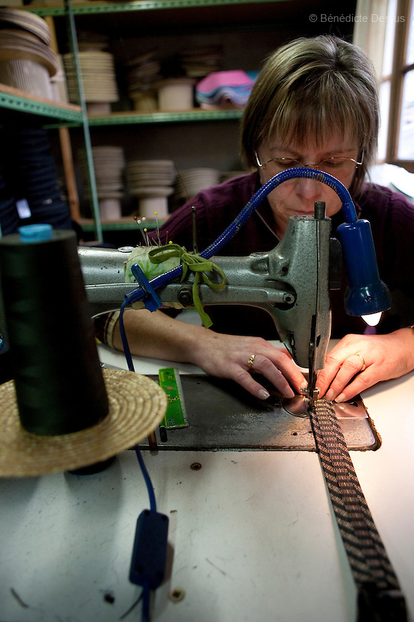 9 december 2009 - Coustilleres' hat factory, Septfonds, France - Claudie Daumont works since 6 years at the Coustilleres' hat factory. She is using specially-designed antique sewing machines for hats. The sewing machines are powered by the women's feet operating two treadles..Septfonds is the heart of French straw hat making, due to its very ancient hatter tradition. The hat making industry had its commercial peak in the late 19th century..Coustillères is a family owned hat making factory that has been making straw hats in Septfonds for nearly 100 years. They make hats from straw, felt, and cloth as well as caps. The current owner is Jean-Claude Coustilleres. He is one of the last hat makers of the region..The straw hat making process is very labor intensive and numerous hands are involved. Nearly all of the equipment is over 100 years old, they use the original presses and tools including aluminium molds and sewing machines and dye their own straw continuing the traditional methods of manufacturing. The hat blocking and shaping, straw braids construction and dyeing are all done by hand..The company works on behalf of fashion houses and makes a variety of regional and historical hats. It produces 2 collections a year distributed by a network of salespeople and through a catalog to clients around the world. Photo credit: Benedicte Desrus