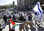 "A Palestinain protester waves his national flag, as Israeli nationalists take part in the ""flag march"" to mark the 48th anniversary of the capture of Arab east Jerusalem in the Six Day War of 1967, in Jerusalem's old city on May 17, 2015. Known as Jerusalem Day, the anniversary marks Israel's seizure and later annexation of the territory, which includes the walled Old City, in a move never recognised by the international community. Photo by Saeb Awad"