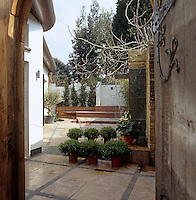 An old-fashioned wooden door opens onto a paved patio garden
