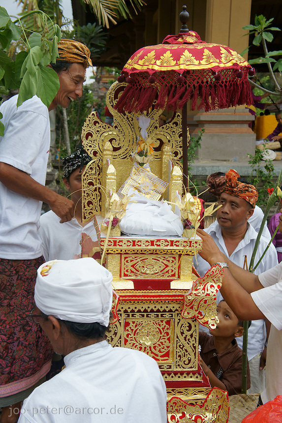 ashes of the passed family member, wrapped in white cotton, are placed on a golden throne to be brought to the sea later in cremation ceremonies,  September 17th 2011,  family Budiana and others,Banjar Pande, Peliatan next to Ubud, Bali, Indonesia. Cremation ceremonies in Bali guide the spirit of the passed family member from underworld death realms to divine heavenly nature spirit life circle uprise of the death, becoming a divine ancestor to be reborn in the next generation of the family