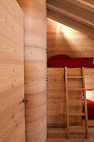 The attic bedroom is entirely clad in wood and has bunk beds